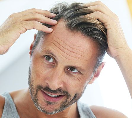 man checking his hair after Micro Needling Treatment for Scalp Hair Growth